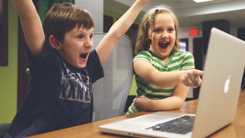 Deux enfants sont fous de joie devant un ordinateur qui affiche le blog de CityPanel